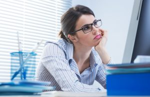 Bored office worker at desk staring at computer screen with hand on chin.