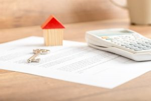 Silver house key lying on a contract for house sale, lease, insurance or mortgage in a real estate concept, viewed low angle with focus to the tip.